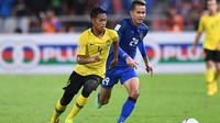 Pemain Timnas Malaysia, Syahmi Safari (kiri), saat melawan Timnas Thailand di leg kedua semifinal Piala AFF 2018 di Stadion Rajamangala, Bangkok (5/12/2018).  (AFP/Lillian Suwanrumpha)