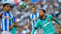 Penyerang Barcelona, Lionel Messi, saat berusaha melewati hadangan gelandang Real Sociedad, Mikel Merino, pada laga pekan ke-17 La Liga Spanyol di Reale Arena, Sabtu (14/12/2019). (AFP/Ander Gillenea)