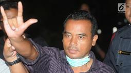 Bupati Purbalingga Tasdi mengacungkan salam saat tiba di Gedung KPK, Jakarta, Selasa (5/6). Tasdi terjaring Operasi Tangkap Tangan KPK bersama lima orang lainya yakni sejumlah pejabat daerah Purbalingga dan pihak swasta. (Merdeka.com/Dwi Narwoko)