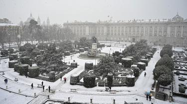 Orang-orang berjalan melewati salju di luar Istana Kerajaan, Madrid, Spanyol, Jumat (8/1/2021). Badai Filomena mengakibatkan salju lebat turun di Madrid dan seluruh Spanyol. (GABRIEL BOUYS/AFP)
