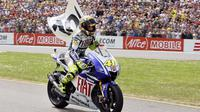Valentino Rossi membawa bendera bertuliskan angka 100 ketika merayakan kemenangannya yang ke-100 dalam balapan MotoGP di sirkuit Assen pada Juni 2009. (AFP/ANP/Vincent Jannink)
