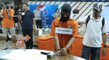 Tersangka HS pelaku kasus pembunuhan satu keluarga di Bekasi (tengah) melakukan pra-rekonstruksi di Polda Metro Jaya, Jakarta, Senin (19/11). 35 adegan diperagakan dari 57 yang akan diperagakan saat rekonstruksi. (Liputan6.com/Helmi Fithriansyah)