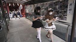 Karyawan mengenakan kostum pelayan dari beberapa kafe bertema pembantu di Akihabara berjalan setelah pertemuan doa untuk perlindungan dari COVID-19 dan untuk bisnis yang berkembang di kuil Kanda Myojin, Tokyo (25/7/2020). (AP Photo/Eugene Hoshiko)
