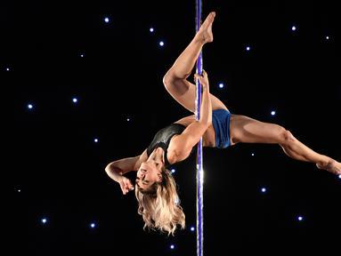 Salah satu peserta, DeAnne Christopher menunjukkan gerakan tari tiang atau pole dance dalam Kejuaraan Pacific Pole 2018 di Los Angeles, Sabtu (7/4). Pole Dance merupakan seni pertunjukan gabungan tari dan akrobat yang menggunakan tiang. (Mark Ralston/AFP)