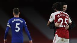 Pelatih Arsenal, Mikel Arteta tersenyum sambil memeluk gelendang Mohamed Elneny usai pertandingan melawan Chelsea pada lanjutan Liga Inggris di Stadion Emirates di London, Minggu (27/12/2020). Sebelum menang atas Chelsea, Arsenal sudah paceklik kemenangan di empat laga. (AFP/Pool/Adrian Dennis)