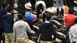 Pembeli, pekerja dan juru lelang menghadiri lelang tuna pada hari pertama pembukaan pasar ikan Toyosu di Tokyo, Kamis (11/9). Pasar ikan Toyosu menggantikan pasar ikan legendaris yang sudah mendunia, Pasar Tsukiji. (Toshifumi KITAMURA/AFP)