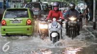 Pengendara motor menerobos genangan air di Pejaten Raya, Jakarta, Selasa (4/10). Akibat curah hujan yang tinggi menyebabkan sejumlah titik di Jakarta tergenang air. (Liputan6.com/Yoppy Renato)