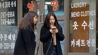 Dua wanita berbincang sambil berjalan di sepanjang jalan di Seoul, Korea Selatan (19/2). (AFP Photo/David Gannon)