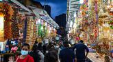 Orang-orang berjalan melintasi sepanjang toko yang menjual ornamen dan dekorasi menjelang Diwali, festival cahaya bagi umat Hindu, di distrik Little India di Singapura pada 23 Oktober 2020. (Photo by Roslan RAHMAN / AFP)