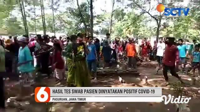 Ratusan orang mendatangi pemakaman pasien positif Covid-19, di Desa Rowogempol, Kecamatan Lekok, Pasuruan, Kamis sore. Massa merebut peti jenazah dan mengeluarkan paksa jenazah, hingga petugas pemakaman yang mengenakan APD lengkap hanya bisa terdiam.
