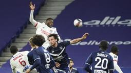 Bek Lyon, Sinaly Diomande (atas) melompat di antara para pemain Bordeaux untuk melepaskan sundulan ke gawang Bordeaux dalam laga lanjutan Liga Prancis 2020/21 pekan ke-22 di Groupama Stadium, Jumat (29/1/2021). Lyon menang 2-1 atas Bordeaux. (AP/Laurent Cipriani)