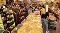 Orang-orang membeli penganan manis saat bulan suci Ramadan di sebuah toko di Baghdad, Irak, pada 3 Mei 2020. (Xinhua/Khalil Dawood)