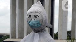 Patung bermasker terlihat di pinggiran Kali Kanal Barat, Cakung, Jakarta, Kamis (25/2/2021). Sebanyak 73.014 spesimen diperiksa hari ini di seluruh Indonesia, sedangkan jumlah suspek COVID-19 sebanyak 77.512. (merdeka.com/Imam Buhori)