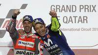 Pebalap Ducati, Andrea Dovizioso bersama Valentino Rossi (kanan) merayakan gelar juara MotoGP Qatar di Sirkuit Losail, Doha, Minggu (18/3/2018). Dovizioso juara dengan catatan waktu 42 menit 34,654 detik. (AFP/Karim Jaafar)