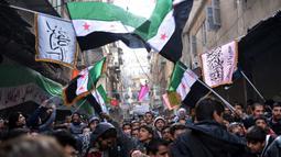 Pengunjuk rasa antirezim Suriah mengibarkan bendera Suriah pra-Baath, yang sekarang digunakan oleh Tentara Pembebasan Suriah, selama demonstrasi setelah salat Jumat di Distrik Bustan al-Qasr, Aleppo, Suriah, 8 Februari 2013. (Photo by AAMIR QURESHI/AFP)