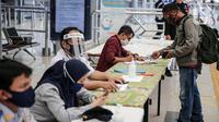Calon penumpang melapor kepada petugas di Stasiun Pasar Senen, Jakarta, Jumat (10/7/2020). PT KAI telah mengoperasikan lima perjalanan kereta jarak jauh untuk tujuan Bandung, Cirebon, dan Surabaya mulai Jumat 10 Juli 2020. (Liputan6.com/Faizal Fanani)