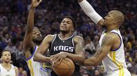 Pemain Sacramento Kings, Rudy Gay (tengah) mencoba melakukan tembakan saat dihadang pemain Golden State Warriors 'pada laga NBA di Golden 1 Center, Sacramento, (8/1/2017). Warriors menang 117-106. (AP/Rich Pedroncelli)