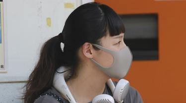 Seorang wanita mengenakan masker wajah untuk membantu melindungi dari penyebaran coronavirus menggunakan kipas angin portabel di lehernya untuk melindungi tubuh dari panas di Tokyo, Rabu, (5/8/2020). (AP Photo/Koji Sasahara)