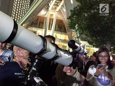 Pengunjung menggunakan teropong untuk melihat berlangsungnya fenomena gerhana bulan total di Taman Ismail Marzuki, Jakarta, Rabu (31/1). Kegiatan nonton bareng Super Blue Blood Moon ini digelar di Planetarium Jakarta. (Liputan6.com/Immanuel Antonius)