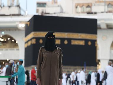 Seorang polisi wanita Saudi berjaga-jaga saat jemaah mengelilingi Ka'bah pada rangkaian ibadah haji di Masjidil Haram, Makkah, Selasa (20/7/2021). Kini, para personel perempuan bergabung dengan rekan-rekan pria mereka dalam menjaga kota suci selama musim haji. (Fayez Nureldine / AFP)