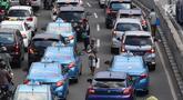 Pedagang asongan menjajakan barang dagangannya di persimpangan lampu merah di Jakarta, Jumat (22/2). Keahlian yang terbatas menyebabkan sebagian orang harus bekerja di tengah padatnya kendaraan Ibukota. (Liputan6.com/Immanuel Antonius)