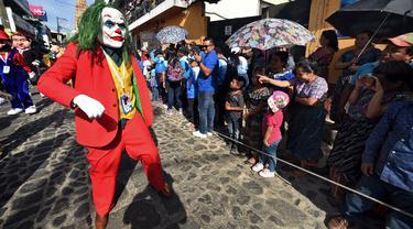 Anggota Saturno Club dengan kostum Joker melakukan parade Dance of Costumes tahunan di sepanjang jalan kota Sumpango, Guatemala, Senin (30/12/2019). Parade kostum yang menampilkan karakter televisi dan film ini untuk memeriahkan malam pergantian tahun. (ORLANDO ESTRADA/AFP)