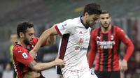 Gelandang AC Milan, Hakan Calhanoglu berebut bola dengan bek Cagliari, Luca Ceppitelli pada pekan ke-37 Serie A di San Siro, Senin (17/5/2021) dini hari WIB.  AC Milan gagal menjauh di klasemen Liga Italia usai imbang 0-0 lawan Cagliari. (AP Photo/Luca Bruno)