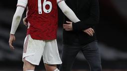 Pelatih Arsenal, Mikel Arteta (kanan) memberi selamat kepada bek Rob Holding usai pertandingan melawan Chelsea pada lanjutan Liga Inggris di Stadion Emirates di London, Minggu (27/12/2020). Mikel Arteta berharap, kemenangan ini menjadi titik kebangkitan timnya. (AFP/Pool/Adrian Dennis)