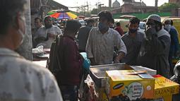 Orang-orang membeli kurma di sepanjang jalan menjelang bulan suci Ramadhan di Delhi, India pada Selasa (13/4/2021). Kurma sangat identik dengan bulan Ramadhan, karena buah yang satu ini kerap dijadikan pengisi menu sahur dan berbuka puasa. (Sajjad HUSSAIN / AFP)