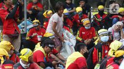 Pemulung berada di tengah-tengah aksi unjuk rasa di kawasan Patung Kuda, Jakarta, Selasa (10/11/2020). Beberapa pemulung mencoba peruntungan saat massa gabungan dari berbagai organisasi buruh dan mahasiswa berunjuk rasa menolak Omnibus Law UU Cipta Kerja. (Liputan6.com/Helmi Fithriansyah)