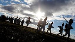Sejumlah orang berjalan berbaris dengan mengenakan pakaian tentara tahun 1800-an di dekat desa Moravian selatan Herspice, Republik Ceko (2/11). Mereka mencoba merekayasa kembali pertempuran Austerlitz. (Reuters/David W Cerny)