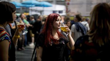 Seorang wanita menikmati minum bir selama The Great British Beer Festival di Kensington Olympia di London barat (6/8/2019). Great British Beer Festival tahunan ini diadakan 6-10 Agustus 2019. (AFP Photo/Tolga Akmen)