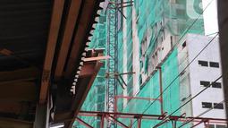 Kereta commuterline melintas dekat proyek pembangunan Apartemen Mahata Tanjung Barat di sekitar Stasiun Tanjung Barat, Jakarta, Kamis (30/1/2020). Apartemen Mahata Tanjung Barat dibangun di atas lahan seluas 15.244 meter persegi dan akan memiliki hunian sebanyak 1.216 unit. (Liputan6.com/Immanuel An