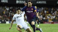 Lionel Messi melewati pemain Valencia, Carlos Soler. (AFP/Jose Jordan)