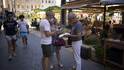 Pemilik restoran memindai kartu kesehatan di sebuah restoran di Marseille, Prancis selatan, Senin (9/8/2021). Prancis mewajibkan semua orang menunjukkan kode QR yang membuktikan mereka memiliki Kartu Vaksinasi untuk memasuki restoran dan kafe atau bepergian di negara tersebut. (AP Photo/Daniel Cole)
