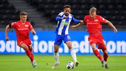 Penyerang Hertha Berlin, Dodi Lukebakio, berebut bola dengan pemain Union Berlin pada laga lanjutan Bundesliga di Stadion Olimpiade, Berlin, Sabtu (23/5/2020) dini hari WIB. Hertha Berlin menang 4-0 atas Union Berlin. (AFP/Stuart Franklin/Pool)