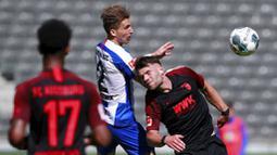 Pemain Hertha Berlin, Peter Pekarik, berebut bola dengan pemain Augsburg, Eduard Lowen, pada laga Bundesliga di Olympiastadion, Sabtu (30/5/2020). Hertha Berlin menang 2-0 atas Augsburg. (AP/Hannibal Hanschke)