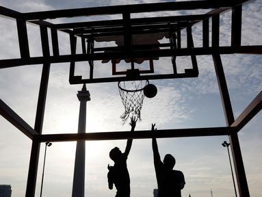 Dua orang warga bermain basket di kawasan Monas, Jakarta, Rabu (13/2). Kawasan Monas menjadi tempat favorit warga Ibu Kota untuk berolahraga. (Bola.com/M Iqbal Ichsan)
