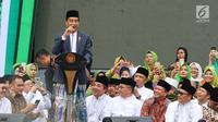 Presiden Joko Widodo atau Jokowi memberi sambutan dalam Harlah ke-73 Muslimat NU di SUGBK, Jakarta, Minggu (27/1). Jokowi datang dengan mengenakan kain sarung, jas, dan kopiah hitam. (Liputan6.com/Johan Tallo)
