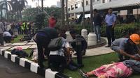 Fransiskus Asisi Wiyono bersama beberapa orang membantu korban runtuhnya lantai balkon Gedung BEI