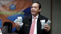 Deputi Pemberantasan Narkotika, Irjen Pol Arman Depari menunjukan barang bukti beserta tersangka saat rilis kasus tindak pencucian uang di BNN, Jakarta, Kamis (24/11). BNN menyita aset senilai Rp 153 Miliar dari tersangka MI. (Liputan6.com/Gempur M Surya)