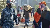 Pengungsi Rohingya membawa barang-barang mereka saat akan dipindahkan ke Pulau Bhasan Char di Chattogram, Bangladesh, Jumat (29/1/2021). Pemindahan itu telah menuai kritik karena keengganan Bangladesh untuk berkonsultasi dengan badan bantuan, termasuk badan pengungsi PBB. (AP Photo/Azim Aunon)