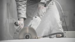 Seniman Italia, Nazareno Biondo menggunakan mesin potong saat menyelesaikan replika mobil Fiat 500 berbahan dasar marmer Carrara di Cafasse, dekat Turin, Italia, Rabu (16/5). (MARCO BERTORELLO/AFP)