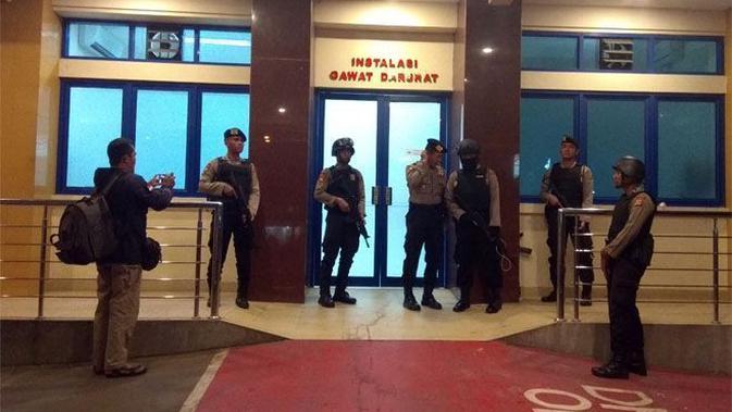 Pintu masuk IGD RS Mitra Plumbon Cirebon dijaga ketat anggota kepolisian bersenjata lengkap, Sabtu (25/8) dini hari. (Wildan Ibnu Walid/JawaPos.com)