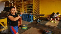 Atlet angkat besi, Sinta Darmariani melakukan pemanasan jelang latihan di luar gedung PB PABBSI, Stadion GBK Jakarta, Senin (11/1/2016). Latihan dilakukan diluar gedung akibat proses renovasi gedung PB PABBSI. (Liputan6.com/Helmi Fithriansyah)