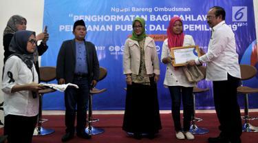 Ketua Ombudsman Amzulian Rifai memberikan piagam penghargaan kepada istri almarhum Ketua KPPS Bekasi saat acara Ngopi Bareng Ombudsman di Ruang Serbaguna Ombudsman RI, Jakarta, Selasa (30/4/2019). Acara ini bertema 'Penghormatan Bagi Pejuang Demokrasi'. (merdeka.com/Iqbal Nugroho)