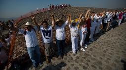Wisatawan mengangkat tangan merasakan hangatnya sinar mentari pada upacara menyambut fenomena equinox di depan Piramida Matahari, Teotihuacan, Meksiko, Senin (20/3). Equinox terjadi dua kali dalam setahun, yakni Maret dan September. (AP/Rebecca Blackwell)