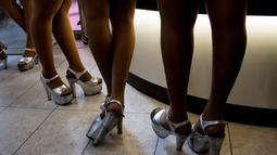 """Pramusaji terlihat di kedai kopi """"Cafe con Piernas"""", pusat kota Santiago, Chile, 26 September 2018. Para pelayan ini mengenakan baju terusan yang ketat dan seksi dengan belahan rendah di bagian dada dan potongan pendek di atas lutut. (Martin BERNETTI/AFP)"""