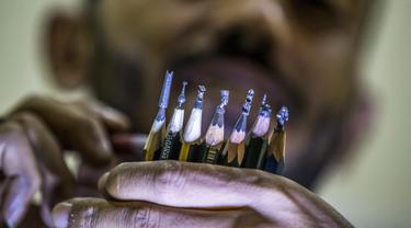 Seniman Ibrahim Bilal memperlihatjan patung-patung Mesir Kuno, sebuah buku, dan masjid yang diukir di ujung pensil di sebuah bengkel di kota Rosetta pada 18 September 2021. Berbekal mikroskop dan beberapa alat ukir, Ibrahim memilih ujung pensil untuk menjadi media karya seninya. (Khaled DESOUKI/AFP)