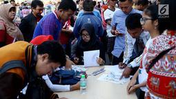 Sejumlah warga mengisi formulir untuk membayar pajak kendaraan bermotor di samsat keliling di car free day, Jakarta, Minggu (27/8). Caranya cukup menggunakan STNK dan membayar pajak sesuai yang tertera. (Liputan6.com/Angga Yuniar)
